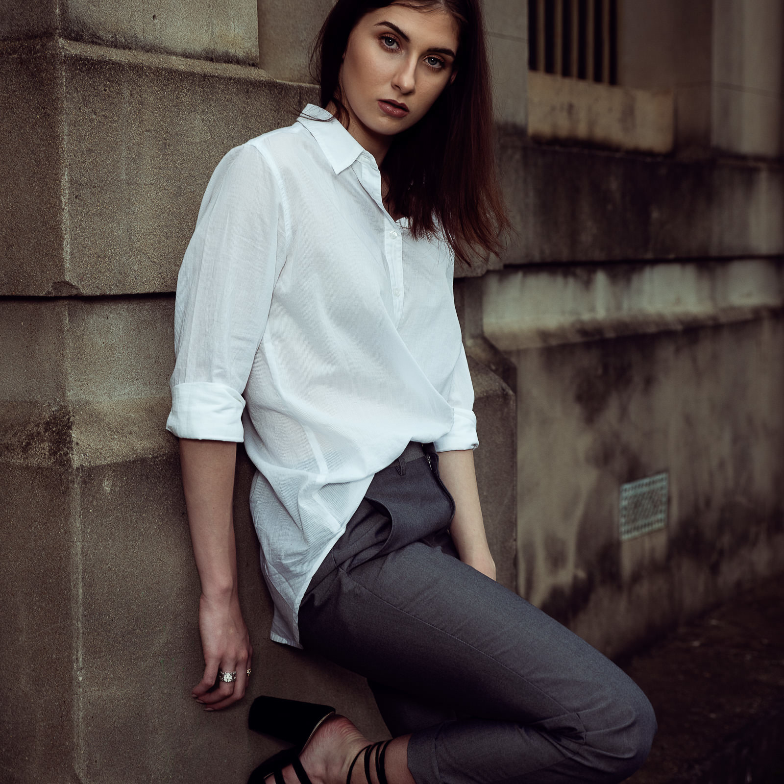 Maddison Hill model in urban environment wearing button up shirt and pants.