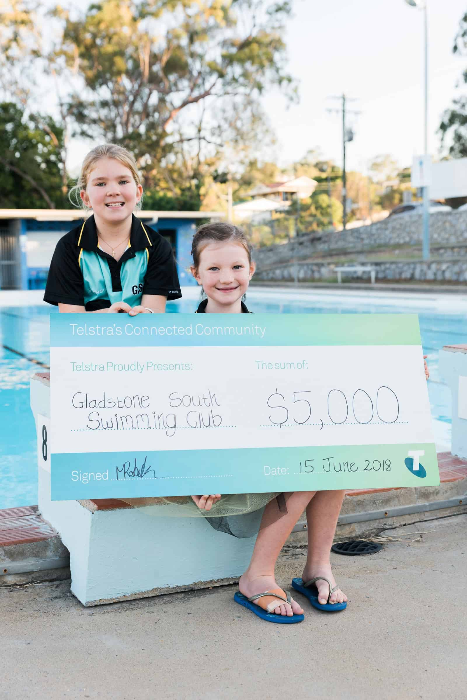 Gladstone South Swimming Club kids hold novelty cheque from Testra