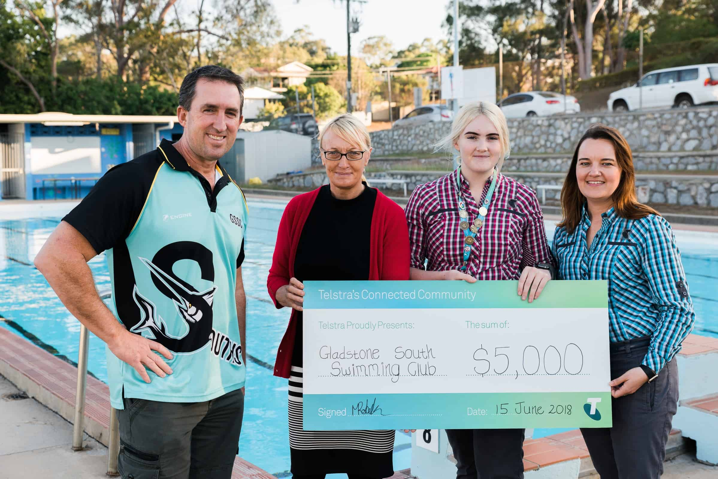 Gladstone South Swimming Club receives cheque from Telstra store representatives.