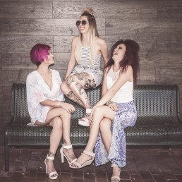 Three girls on a bench laughing