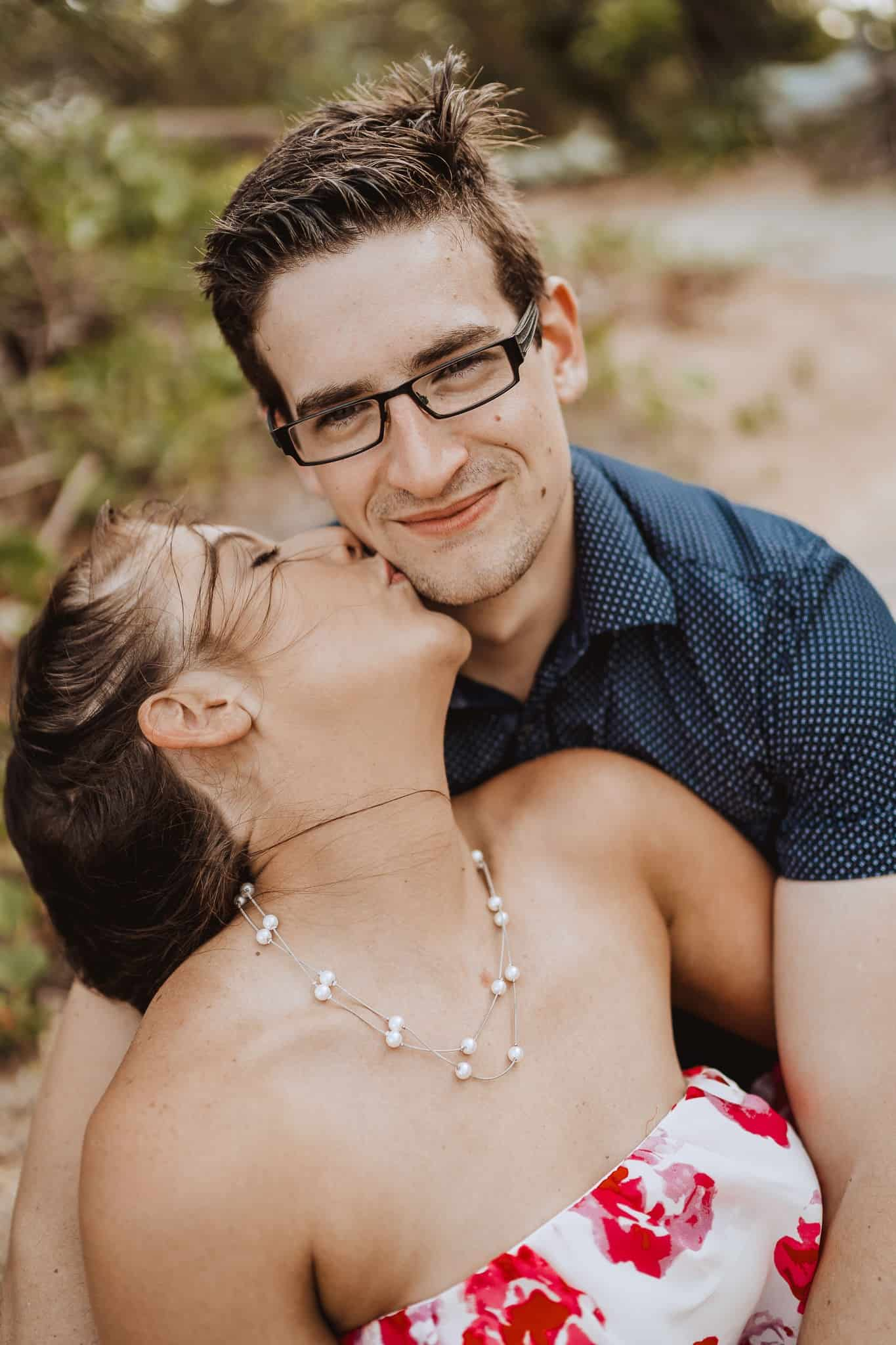 girl kisses boy with glasses