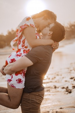 man lifts fiance while kissing on the beach
