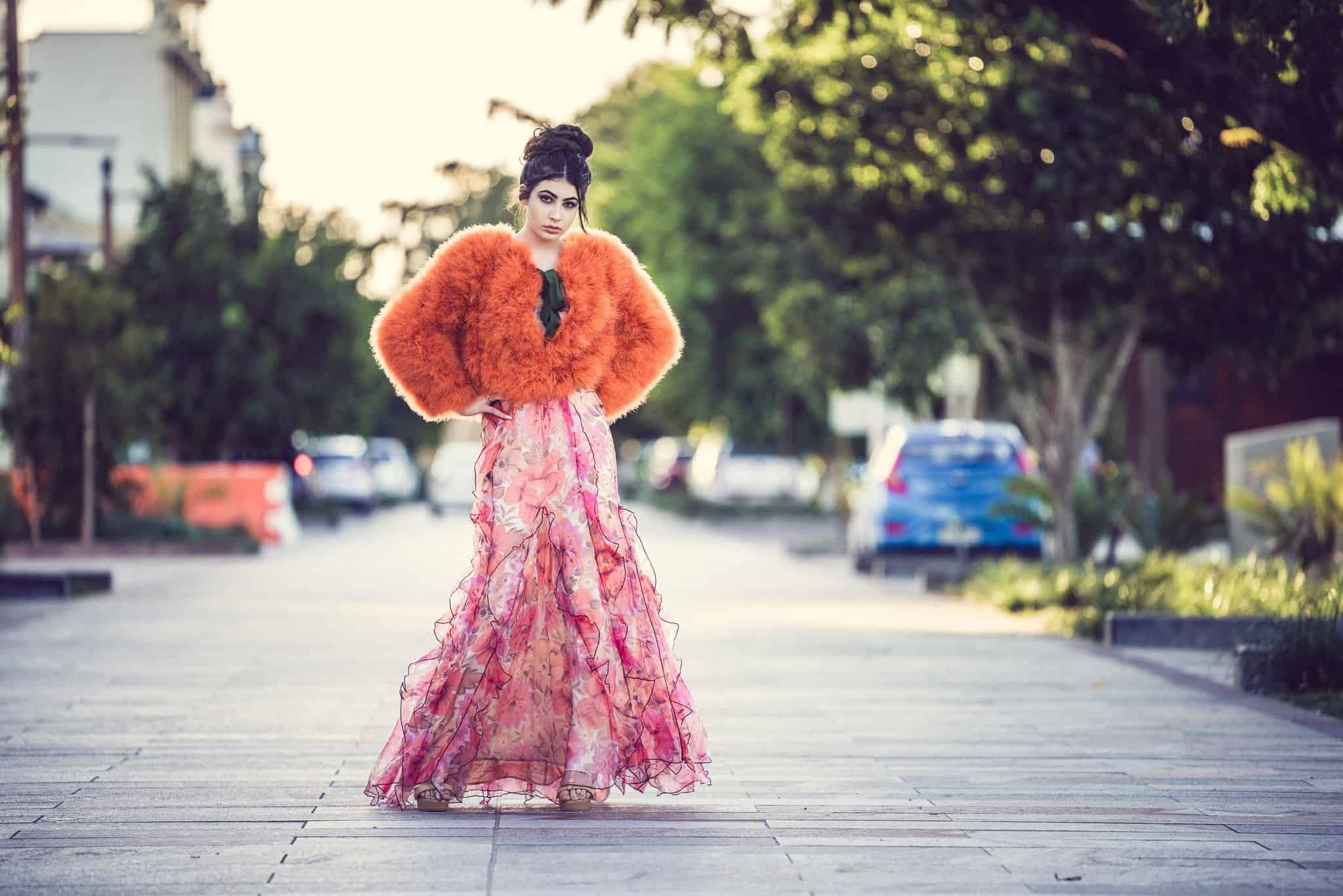 odel in dress and fur coat on the road