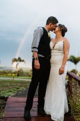 Bride & Groom kissing in front of rainbow