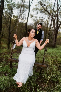 Groom pushing Bride on a swing