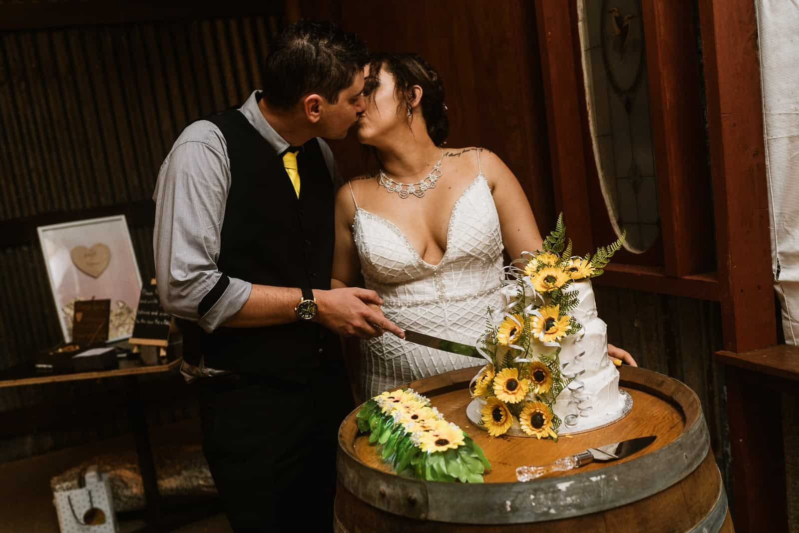 Bride & Groom kiss cutting the cake