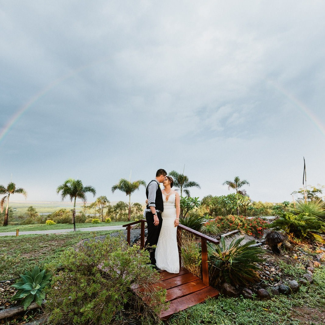 Bride & Groom embrace under a rainbow