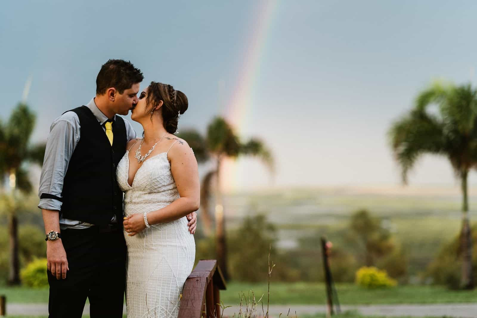 Wedding couple kiss with a rainbow in the background