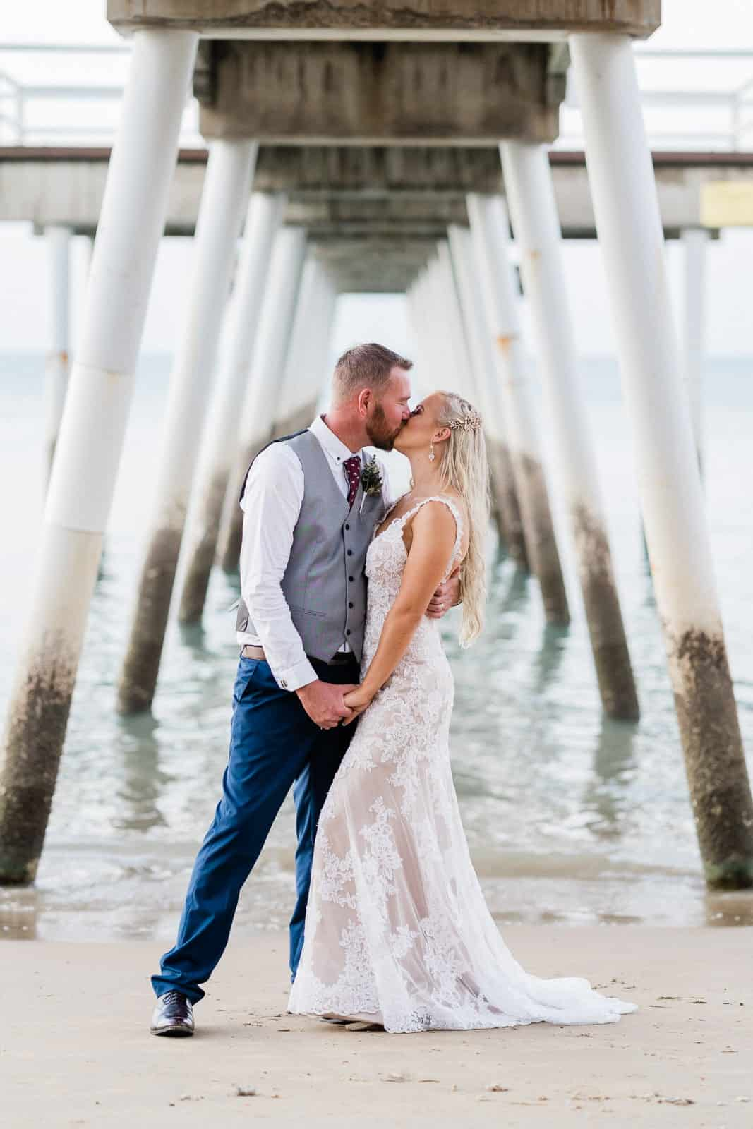 Bride & Groom kiss under Hervey Bay pier