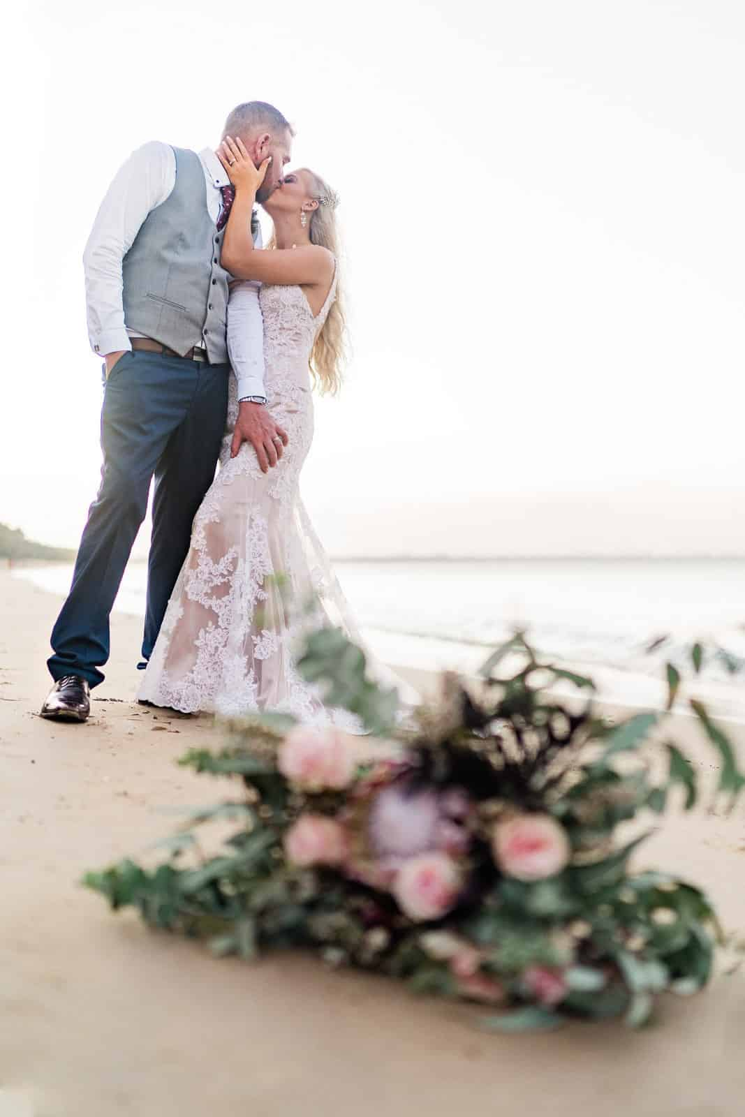 Bride & Groom kiss in front of bouquet on Hervey Bay beach