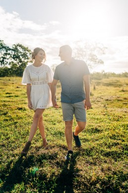 Couple holding hands and walking through field