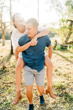 Engaged couple piggy back and laughing