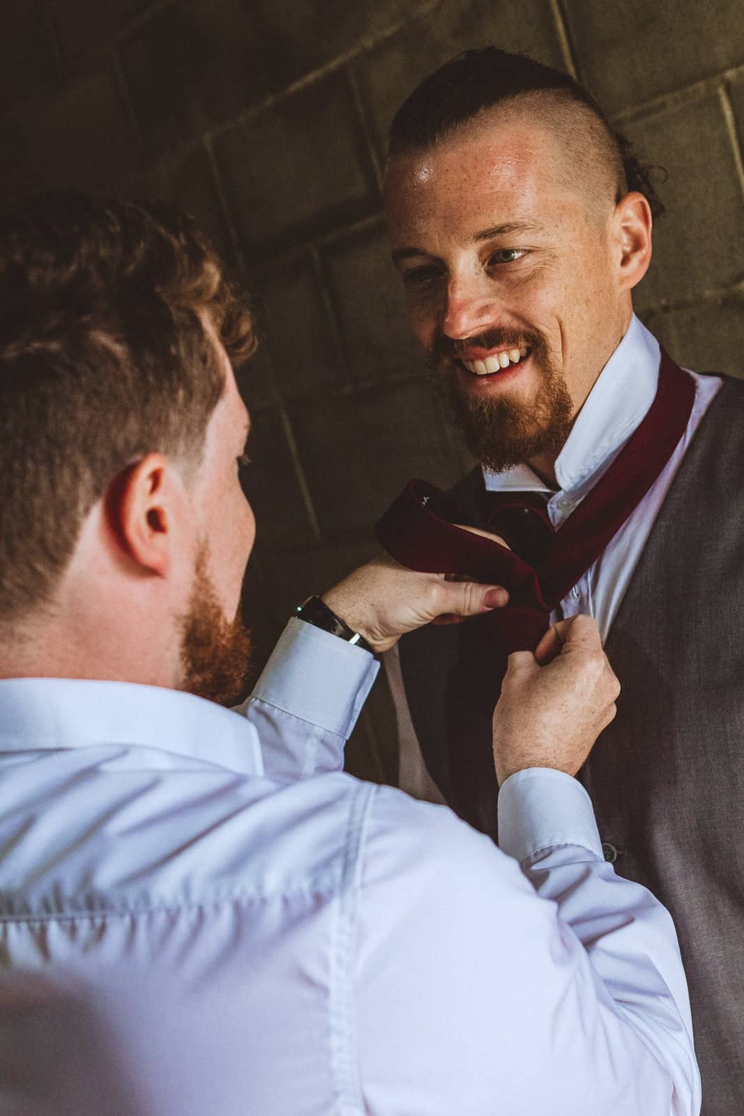 Groom getting help with tie